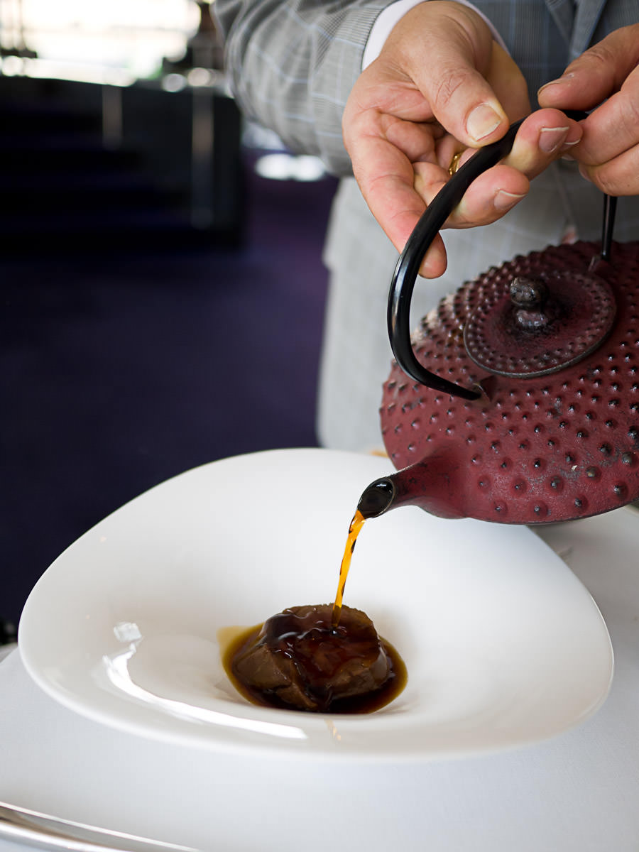 Pouring the oxtail consomme over the pure-bred wagyu, bitter chocolate black pudding