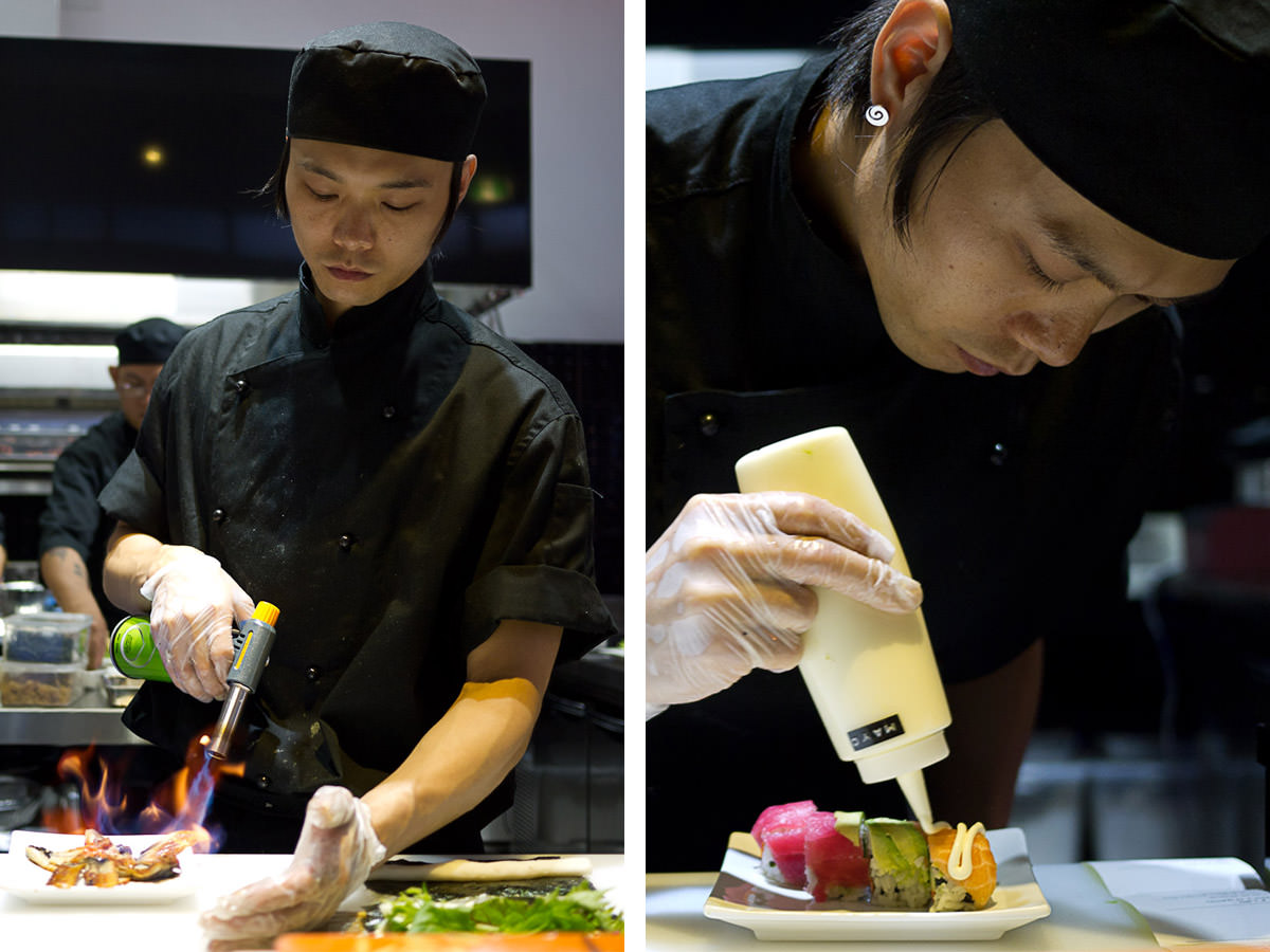 Aisuru sushi chef in action: searing unagi (eel) and drizzling mayonnaise on a rainbow roll