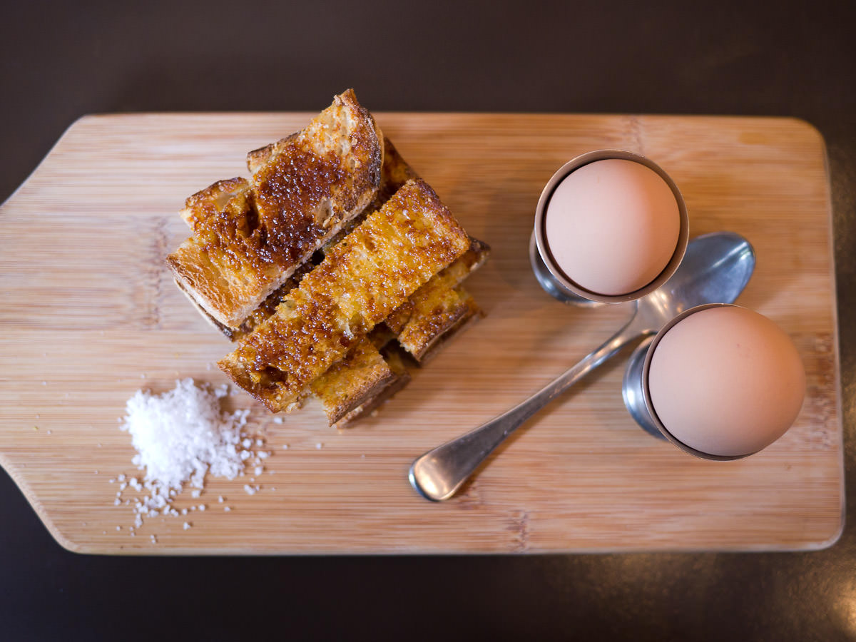 Two soft-boiled eggs with toasted Vegemite sourdough soldiers