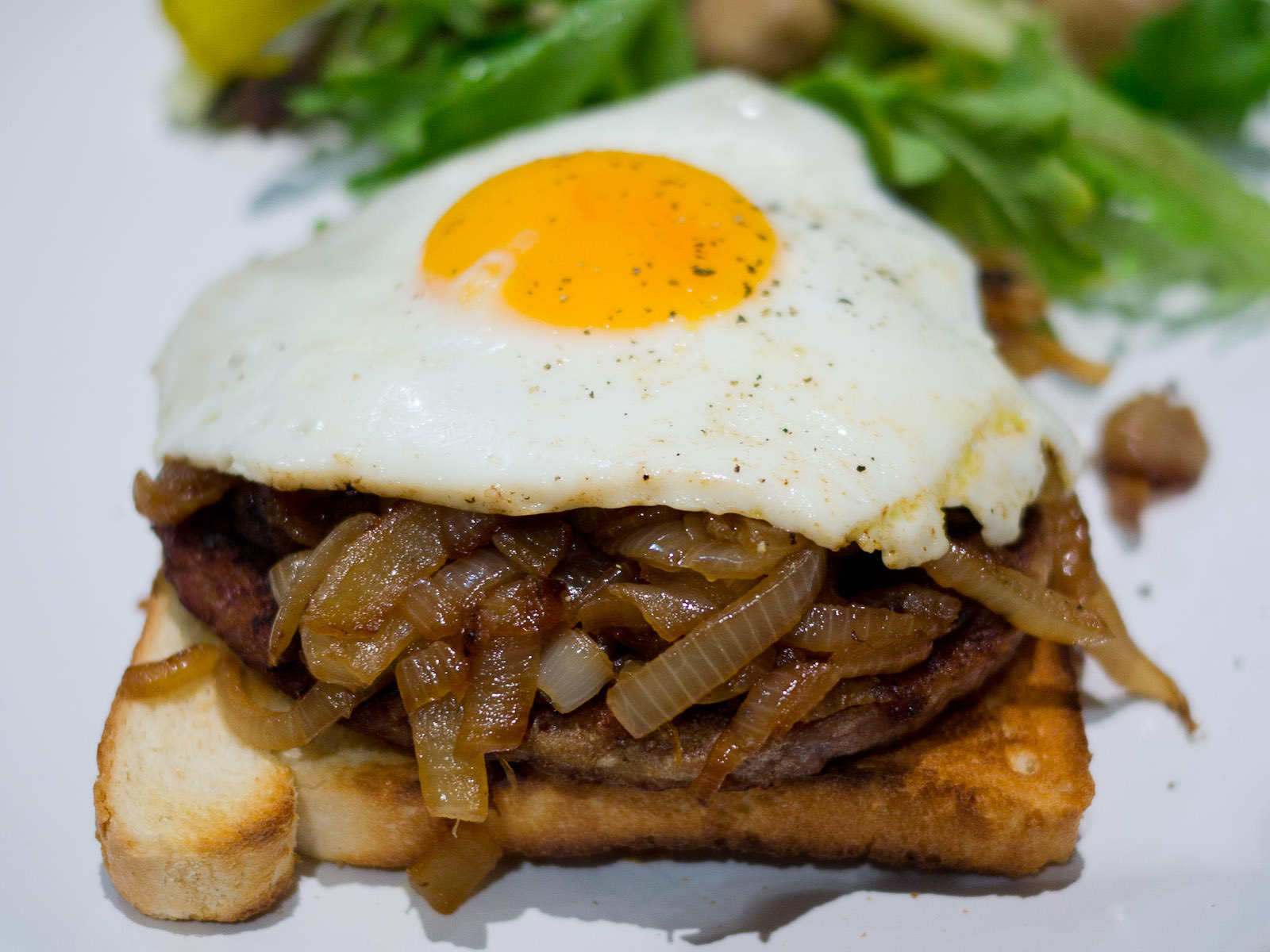 Fried egg, onions and burger pattie on toast with pickles and green salad