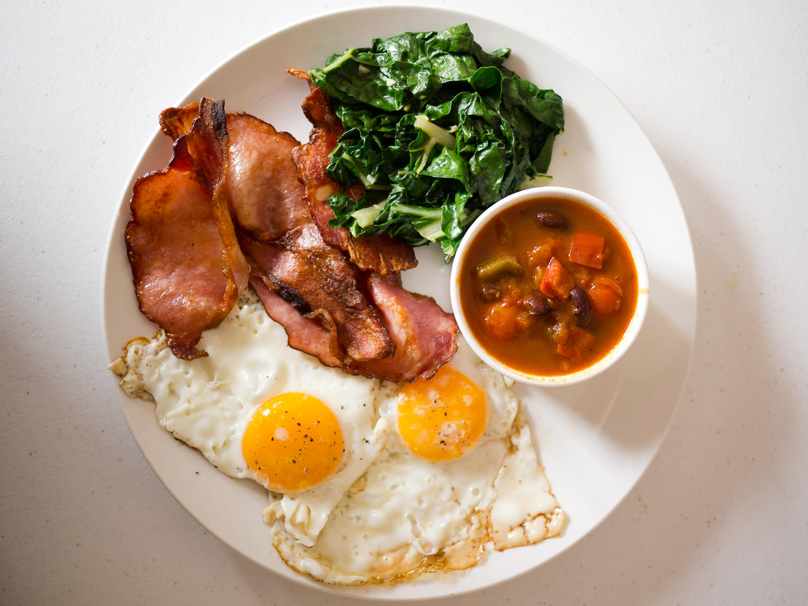 Fried eggs, bacon, garlic silverbeet, and spicy tomato, capsicum and beans