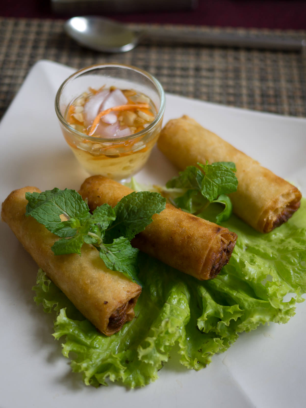 Deep fried spring rolls with chicken, fresh mint and vinegar sauce