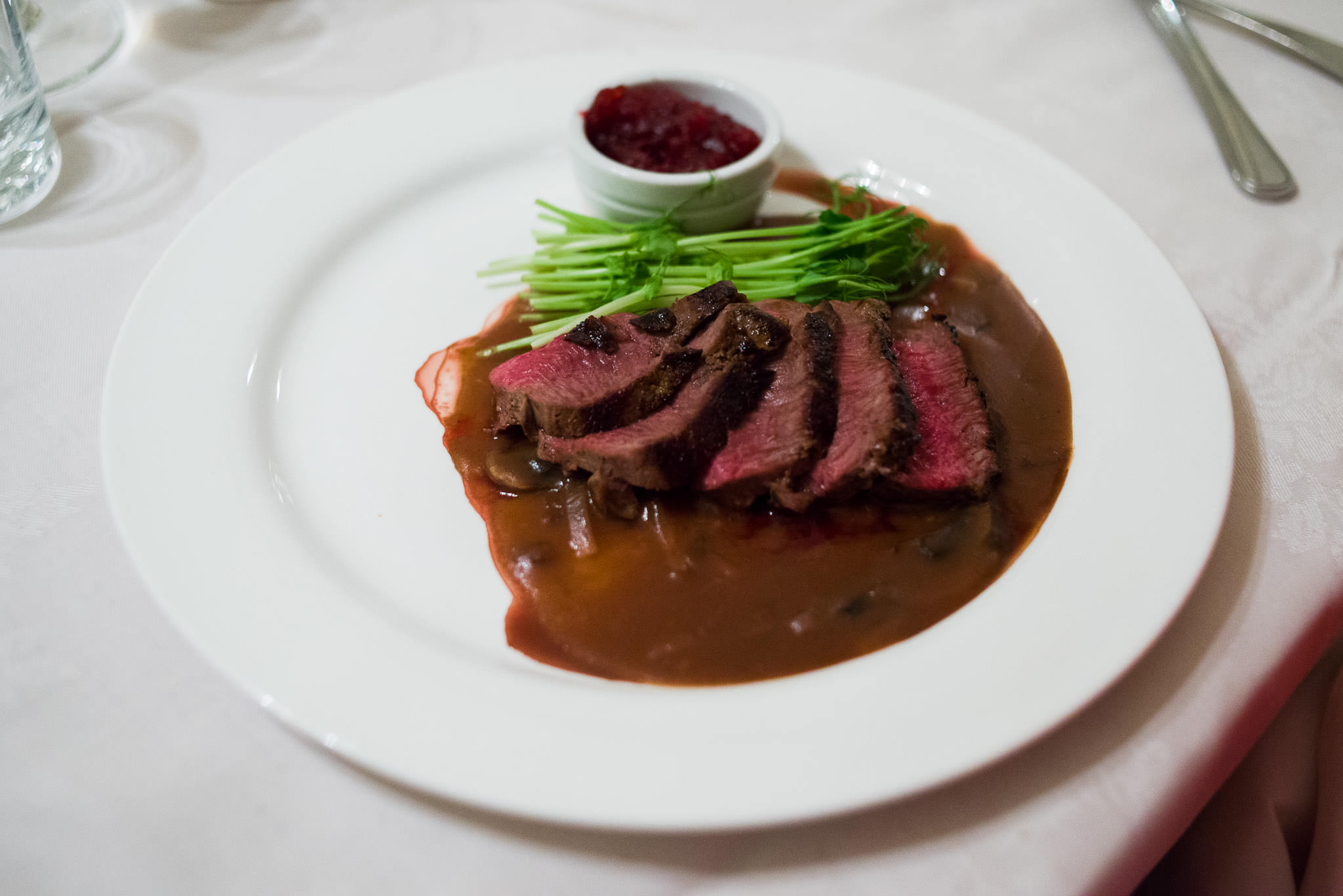 Grilled venison sirloin served on mushroom sauce with cranberry sauce on the side, Conti's, Woodvale