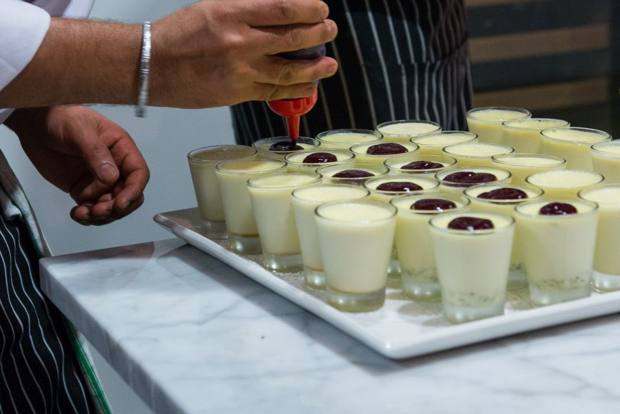 Topping pistachio panna cotta with berry sauce