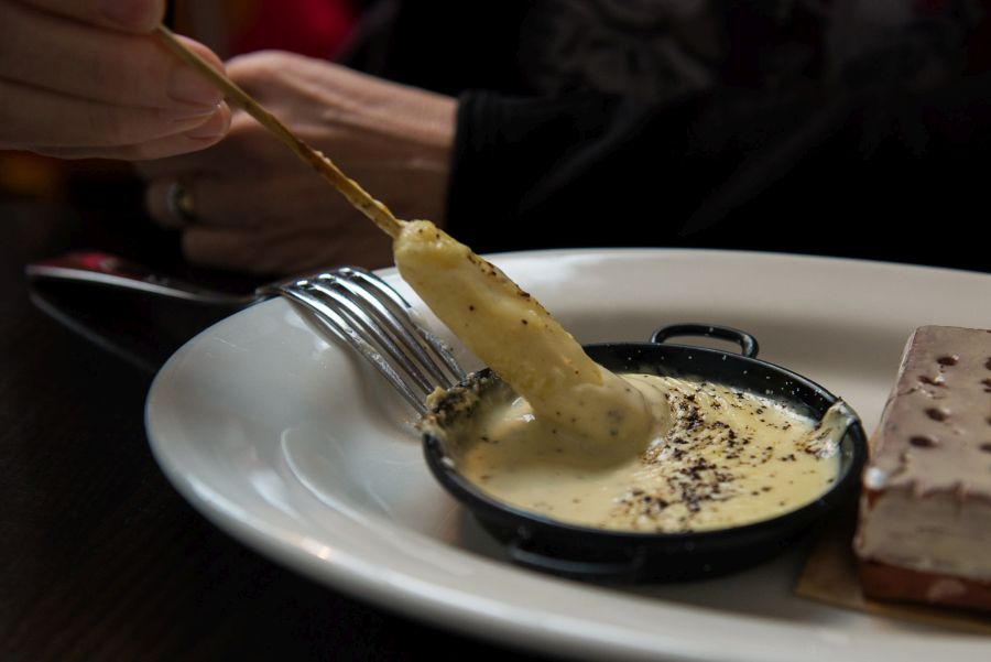 Dipping potato gnocchi into cheese sauce