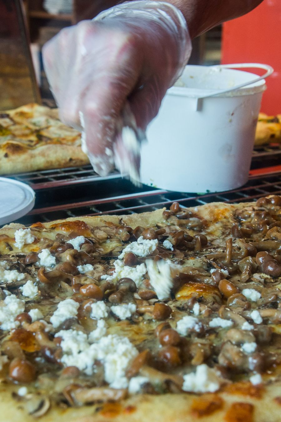 Crumbling ricotta over the mushroom trio pizza