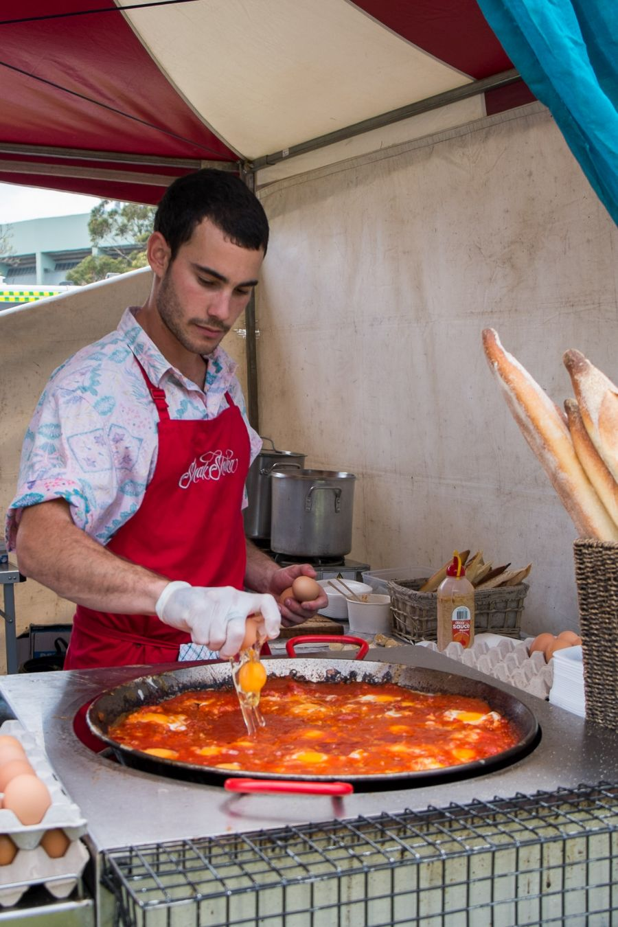 Cracking eggs into the spicy tomato sauce at the Shak Shuka stall