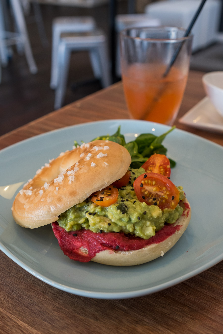 Smashed avocado bagel with beetroot hummus, tomato, black sesame and salad (AU$14.50)
