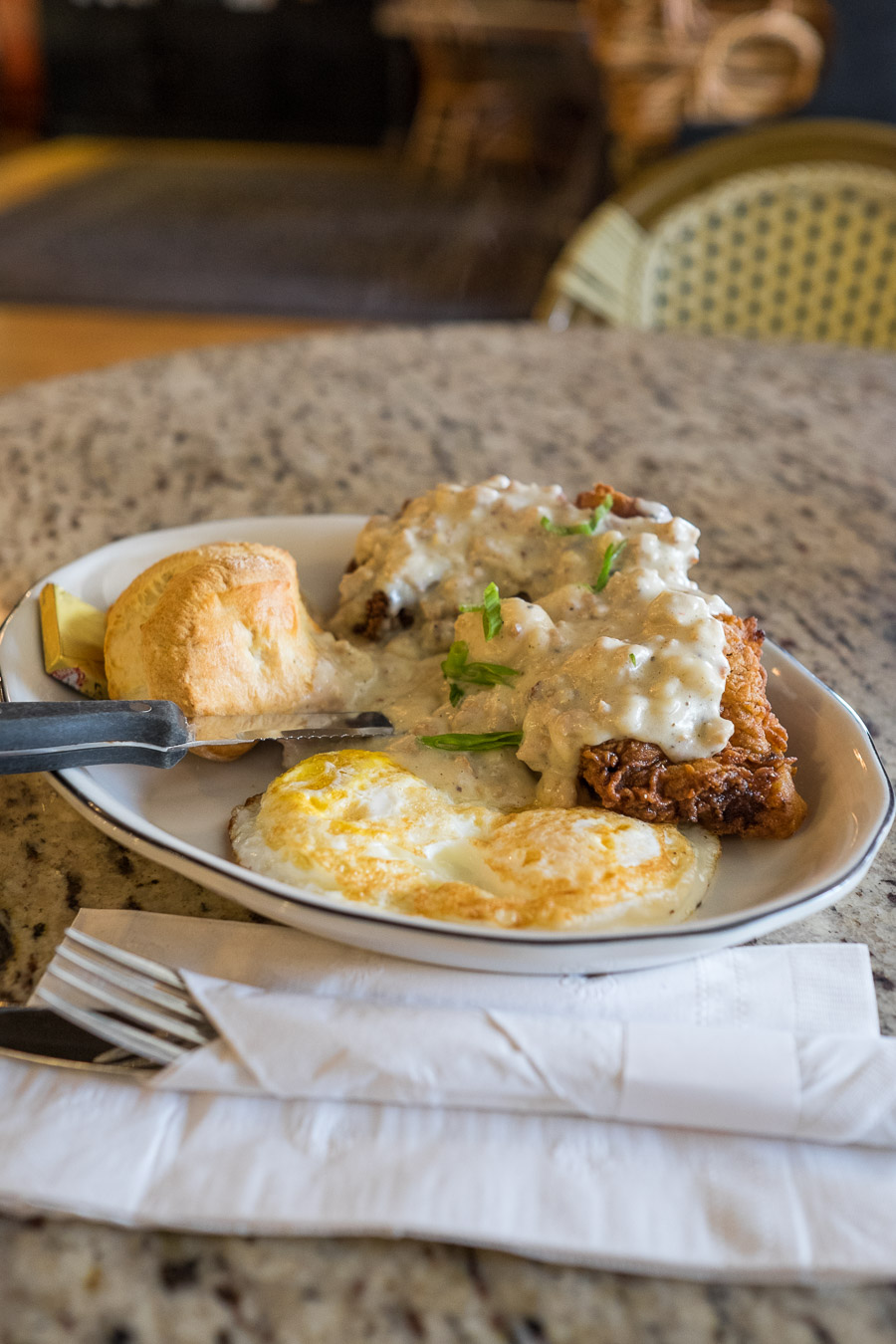 Chicken fried steak with country gravy, two eggs over easy and biscuits