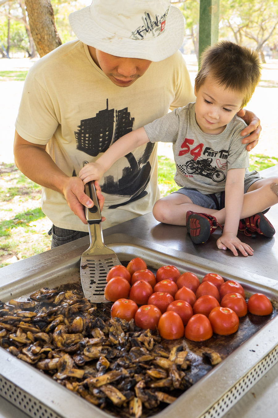 Caleb helps flip the tomatoes