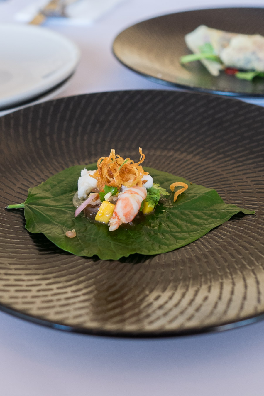Miang of prawn with mango, herbs, coconut milk and lime, served on betel leaf