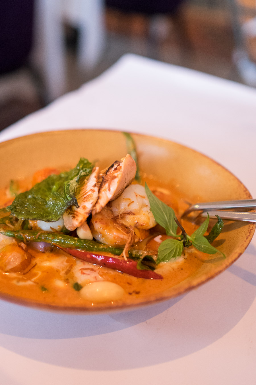 Red curry of fish fillet, prawns and scallops, bean, cherry tomato, pickled garlic and Thai basil