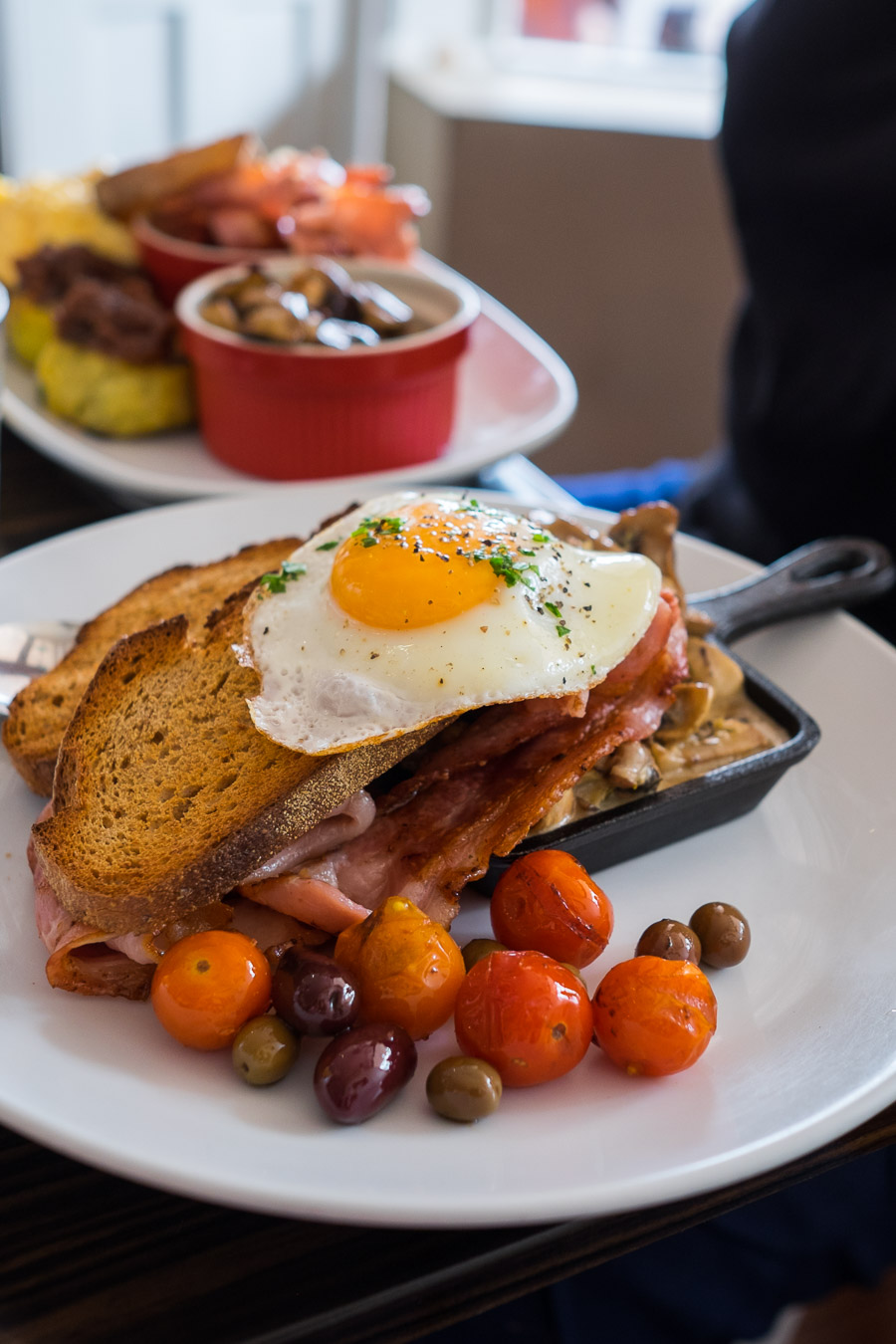 Creamed mushrooms with sunny side egg, bacon, roasted cherry tomatoes, olives and rye toast (AU$18.50)