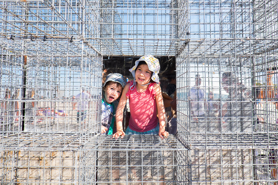 Zoe and Caleb in the House of mirrors by NEON - mirror finish stainless steel, gabion cages