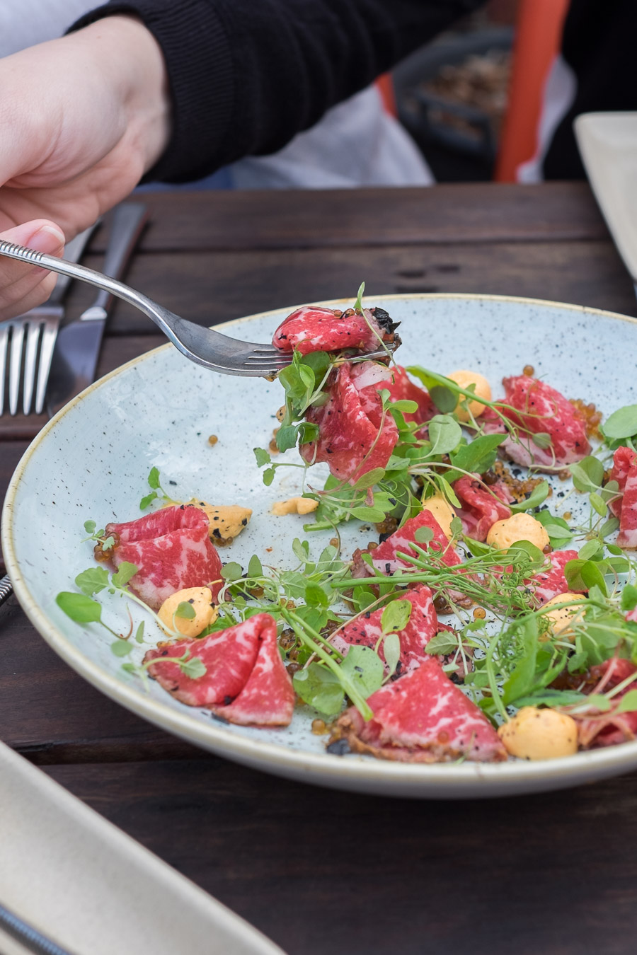 Beef carpaccio - Ranger Valley (NSW) porterhouse rubbed in spice (coriander seed, paprika, pink and black peppercorns), seared and shaved, served with harissa cream, pea shoots and Pedro Ximenez caviar.